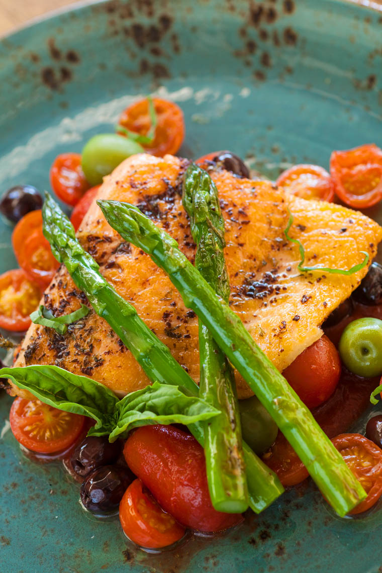 organic Arctic char (sea trout) on a bed of roasted tomatoes topped with asparagus